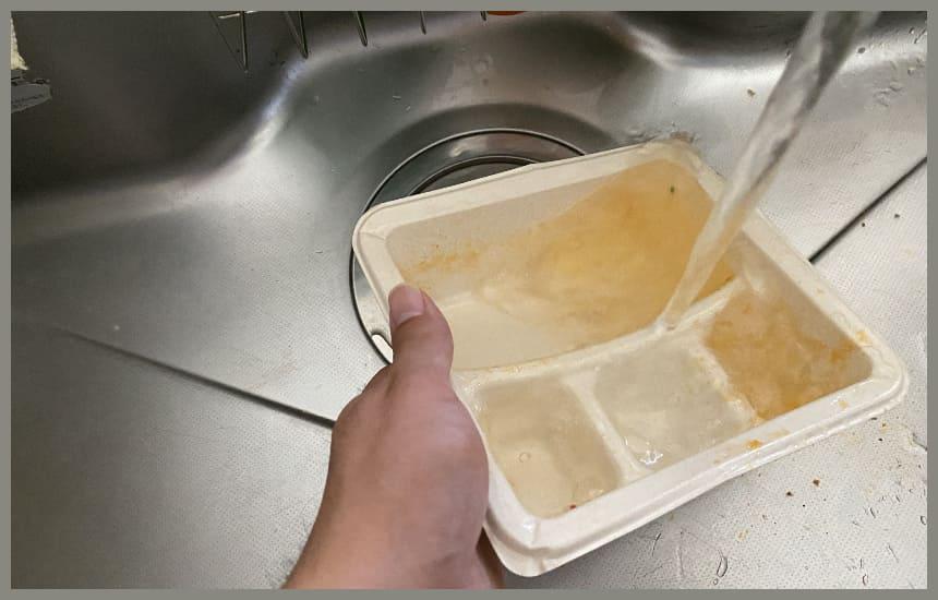 ナッシュの容器を水であらっている