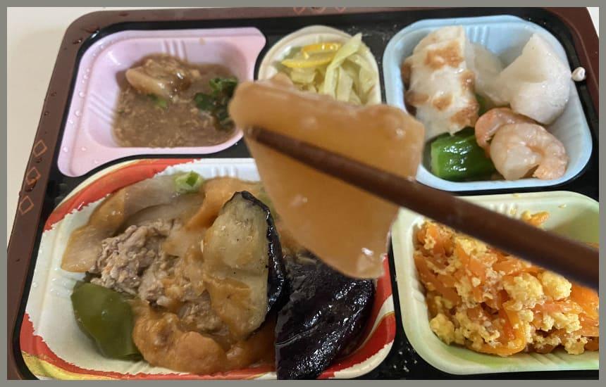 食宅便の3食目の豚肉と茄子の味噌炒めに入っている大根をもっている